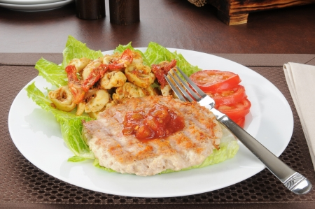Healthy diet lunch with a chicken or turkey burger and tortellini Stock Photo