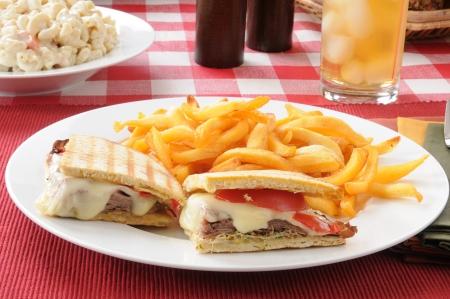 A roast beef panini with fries and macaroni salad photo