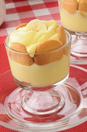 A cup of vanilla pudding with bananas and cookies