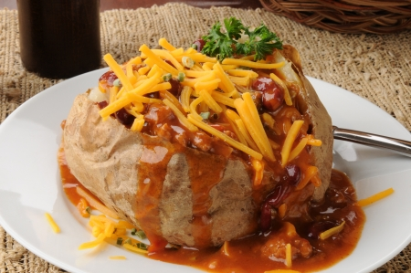A baked potato whti chile, cheese and chives 스톡 콘텐츠