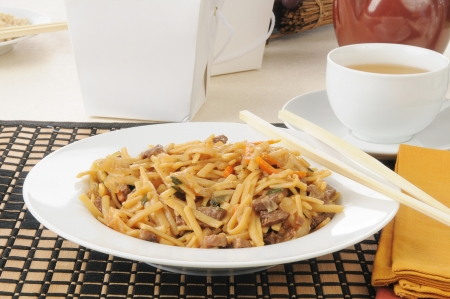 a bowl of beef lo mein with take out containers photo