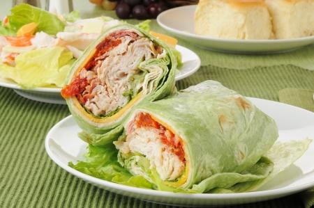 A turkey club sandwich in a spinach tortilla with crab salad