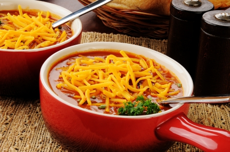 An individual serving crock of chili with meat, topped with cheddar cheese and chives