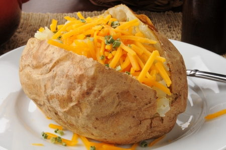 A baked potato with grated cheddar cheese and chives