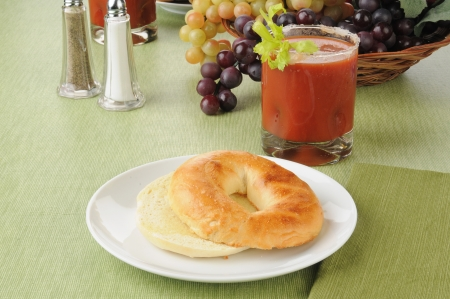A buttered bagel with a bloody mary cocktail