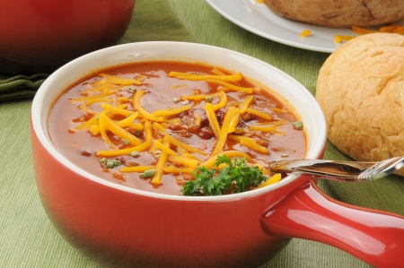 A crock of chili con carne with cheddar cheese