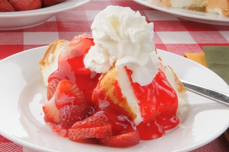 Strawberry shortcake on angle food cake served on a picnic table Standard-Bild