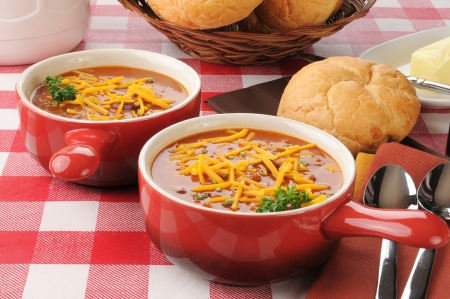 Individual serving crocks of chili con carne with cheddar cheese