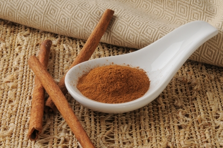 Ground cinnamon in a spoon with cinnamon sticks