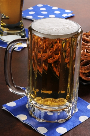 A mug of beer and petzels on a bar counter