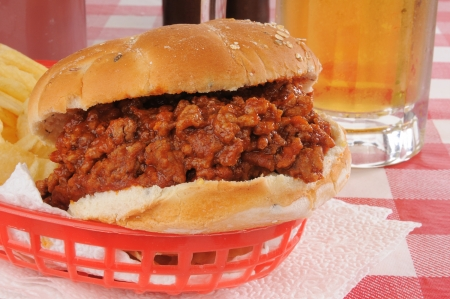 sloppy: Closeup of a sloppy joe with a mug of beer