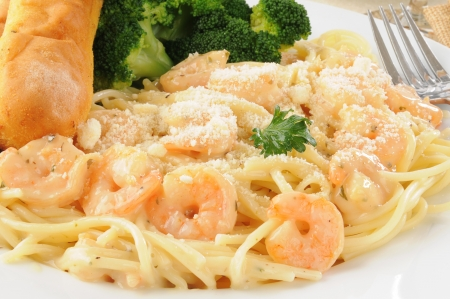 Close up of a plate of shrimp scampi in garlic butter sauce with bread sticks photo