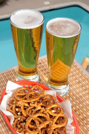 pretzels: Tall glasses of beer by the pool with a basket of pretzels Stock Photo