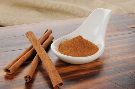 Cinnamon stick and powder on a wooden chopping block
