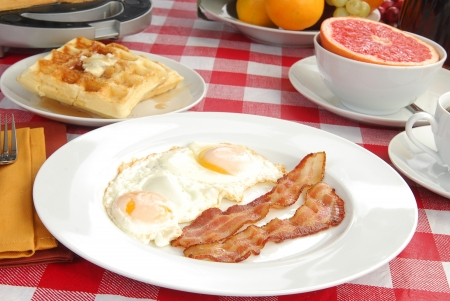 A big breakfast with bacon, eggs, waffles, and pink grapefruit photo