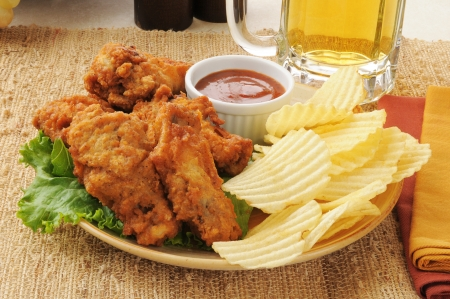 A plate of chicken wings with potato chips and a mug of beer photo