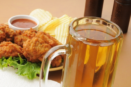 Closeup of a mug of beer with chicken wings and potato chips Stock Photo