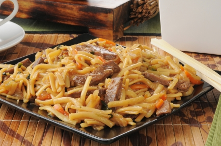 lo mein: A plate of beef lo mein with chopsticks