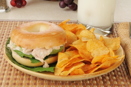 tunafish: A tunafish sandwich on a bagel with potato chips