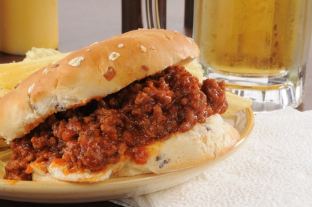 sloppy: Closeup of a sloppy joe hamburger and a mug of beer