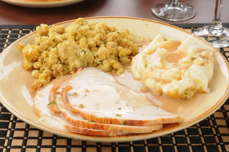 A plate of sliced turkey with mashed potatoes and stuffing