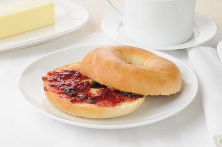 A sliced bagel with strawberry jam and coffee