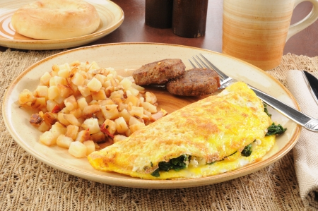 an omelette: A spinach and feta cheese omelet with sausage patties