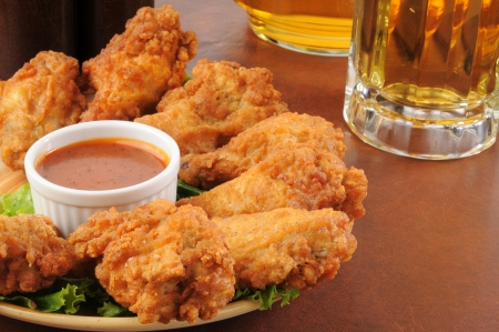 A plate of chicken wings iwth barbecue sauce and beer Standard-Bild