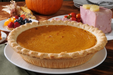 A pumpkin pie on a Thanksgiving dinner table