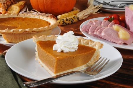 a slice of pumpkin pie on a Thanksgiving dinner table Stock Photo