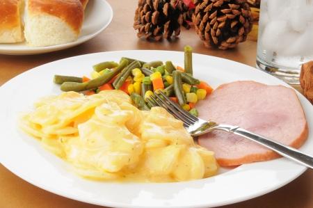 Ham en gegratineerde pottos op een Thanksgving tafel