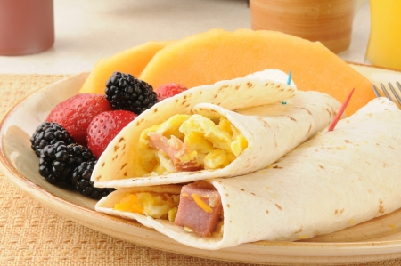A breakfast burrito with fresh berries and fruit Standard-Bild