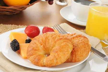 continental: Fresh croissants with cantaloupe and berries Stock Photo