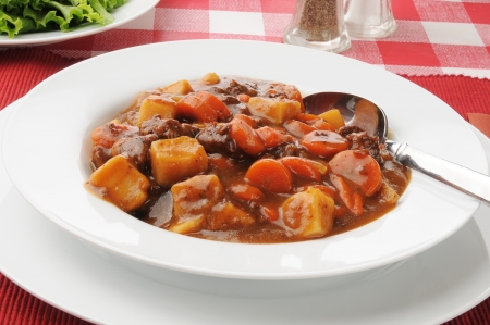 stew: A bowl of beef stew with a green salad