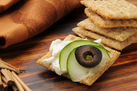 A whole wheat cracker with cream cheese, cucumber and black olive