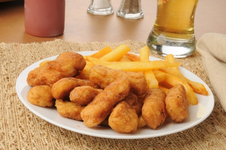 tenders: Honey battered chicken tenders with beer and french fries Stock Photo