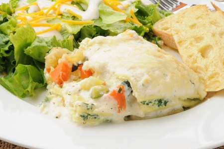 A closeup of vegetable lasagna with garlic toast and salad photo