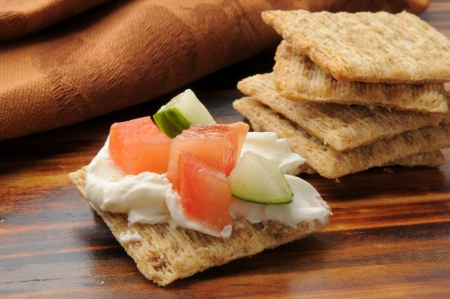 A whole wheat cracker topped with cream cheese, tomato, cucumber, and chives photo