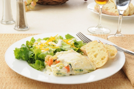 A plate of vegetable lasagna with salad and wine photo