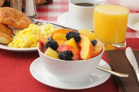 A bowl of fresh fruit with scrambled eggs and croissants Standard-Bild
