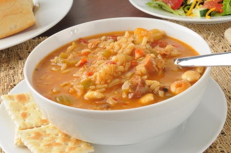 Close up of a bowl of chicken gumbo with a salad and dinner rolls