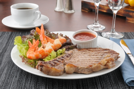 A surf and turf dinner of rib steak and shrimp prawns 스톡 콘텐츠