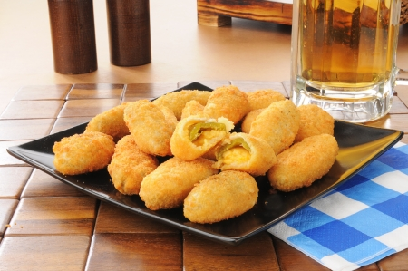 poppers: Jalapeno and cheddar cheese poppers iwth a mug of beer Stock Photo