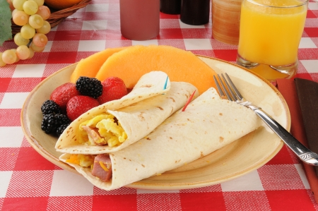 Ham and egg burritos with cantaloupe and berries