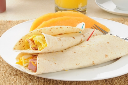 Breakfast burritos with sliced cantaloupe photo