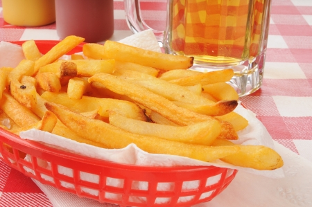 A basket of french fries and a mug of beer photo