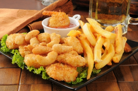 A snack platter with popcorn and coconut shrimp, fries and beer Imagens