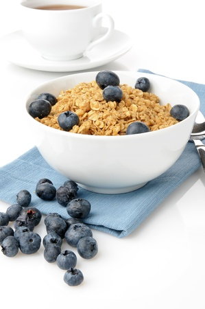 grain and cereal products: A bowl of granola with fresh blueberries on a white background