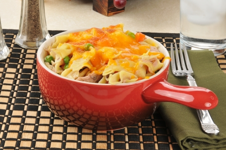 A red serving crock of tuna noodle casserole Imagens
