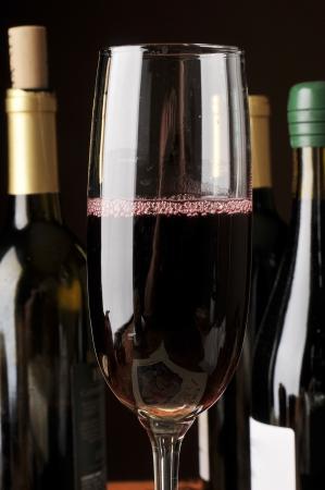 cabernet: Un vaso de vino tinto Cabernet Sauvignon con una variedad de botellas de vino en el fondo